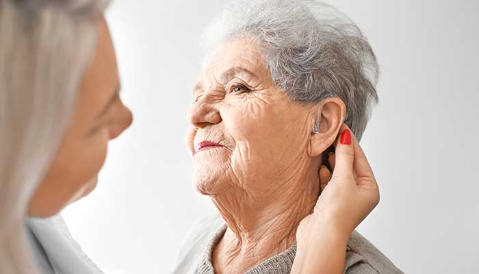 An audiologist checking a patients ear