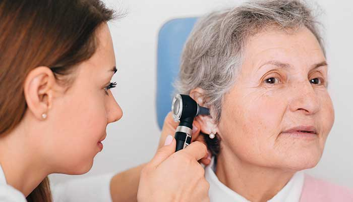 A health practitioner checking an ear canal